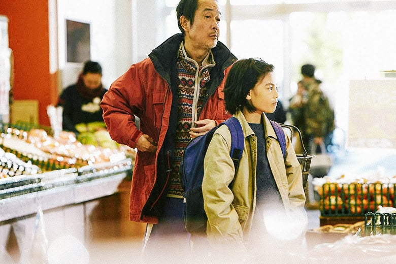 A still from Shoplifters depicts characters Osamu (Lily Franky) and Shota (Jyo Kairi) standing at a grocery store.