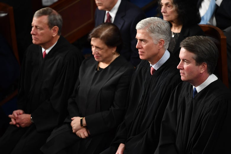 Four Supreme Justices in their justice robes listening intently.