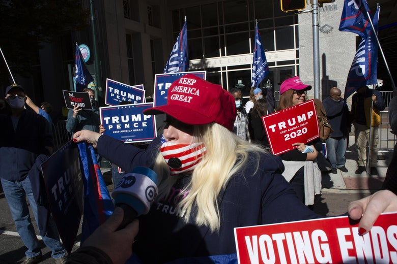 A woman in a MAGA hat and an American flag mask, which sits below her nose.