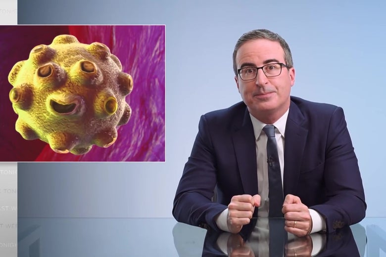 John Oliver sits at an anchorperson desk; a cartoon image of a smiling virus is on the screen behind him.