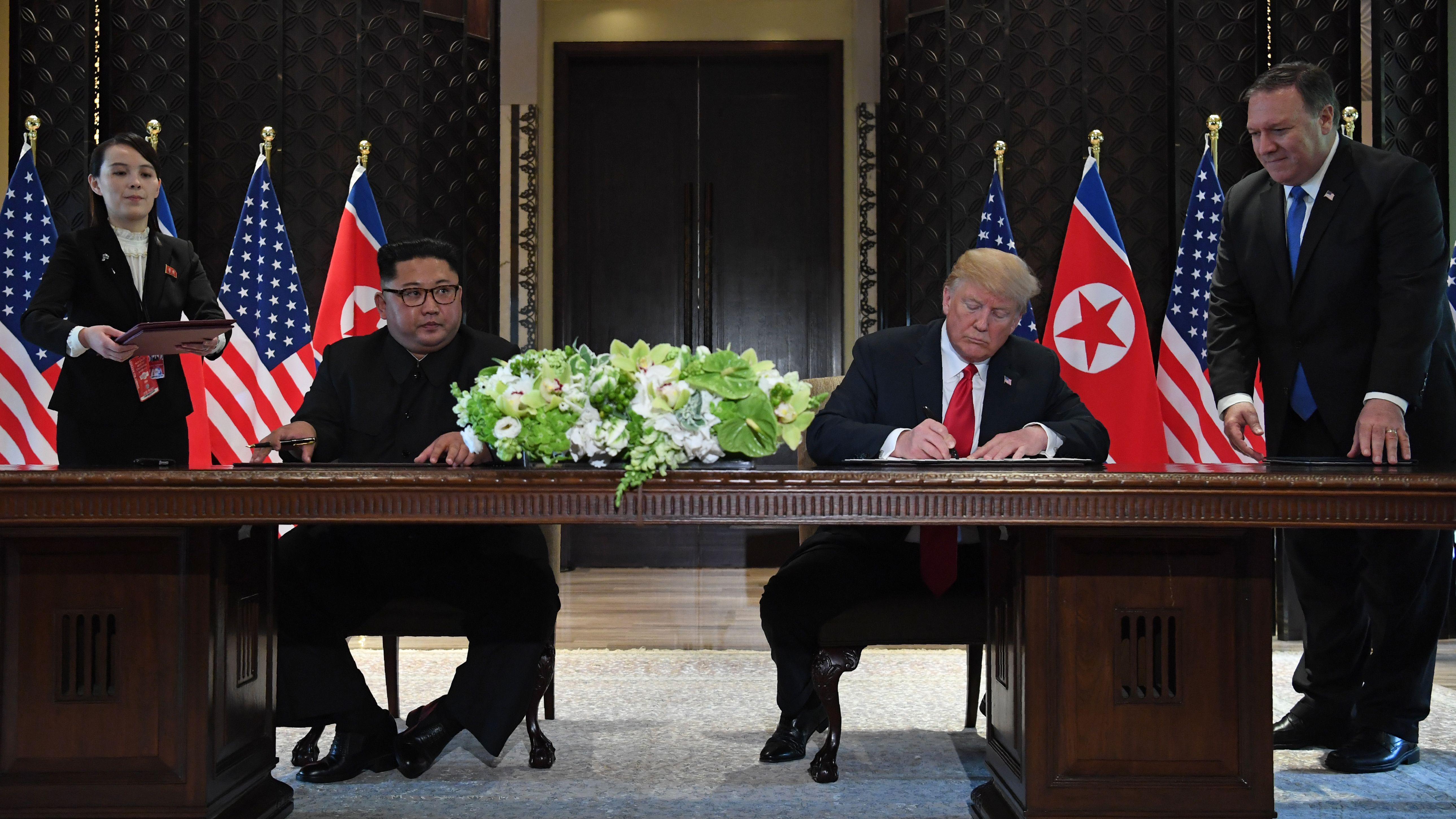 Kim Jong-un and Donald Trump sit at a table and sign the joint statement, with Mike Pompeo standing over Trump.