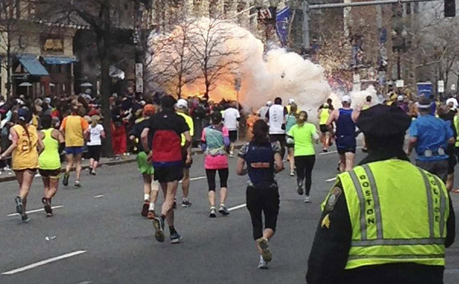 Runners continue to run towards the finish line of the Boston Marathon as an explosion erupts near the finish line.