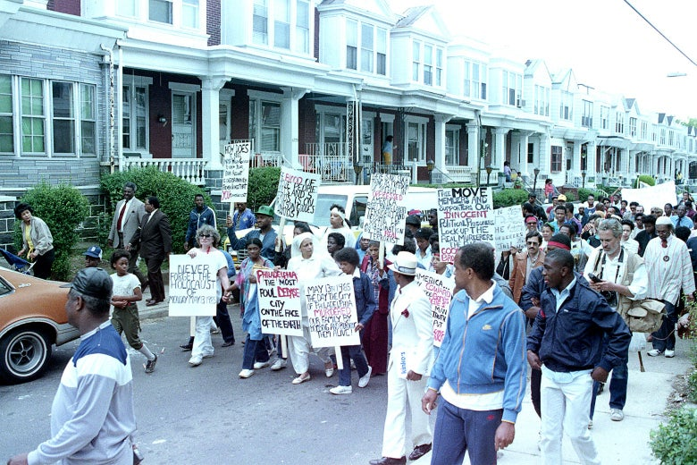 People march in the road past row houses holding signs in support of MOVE