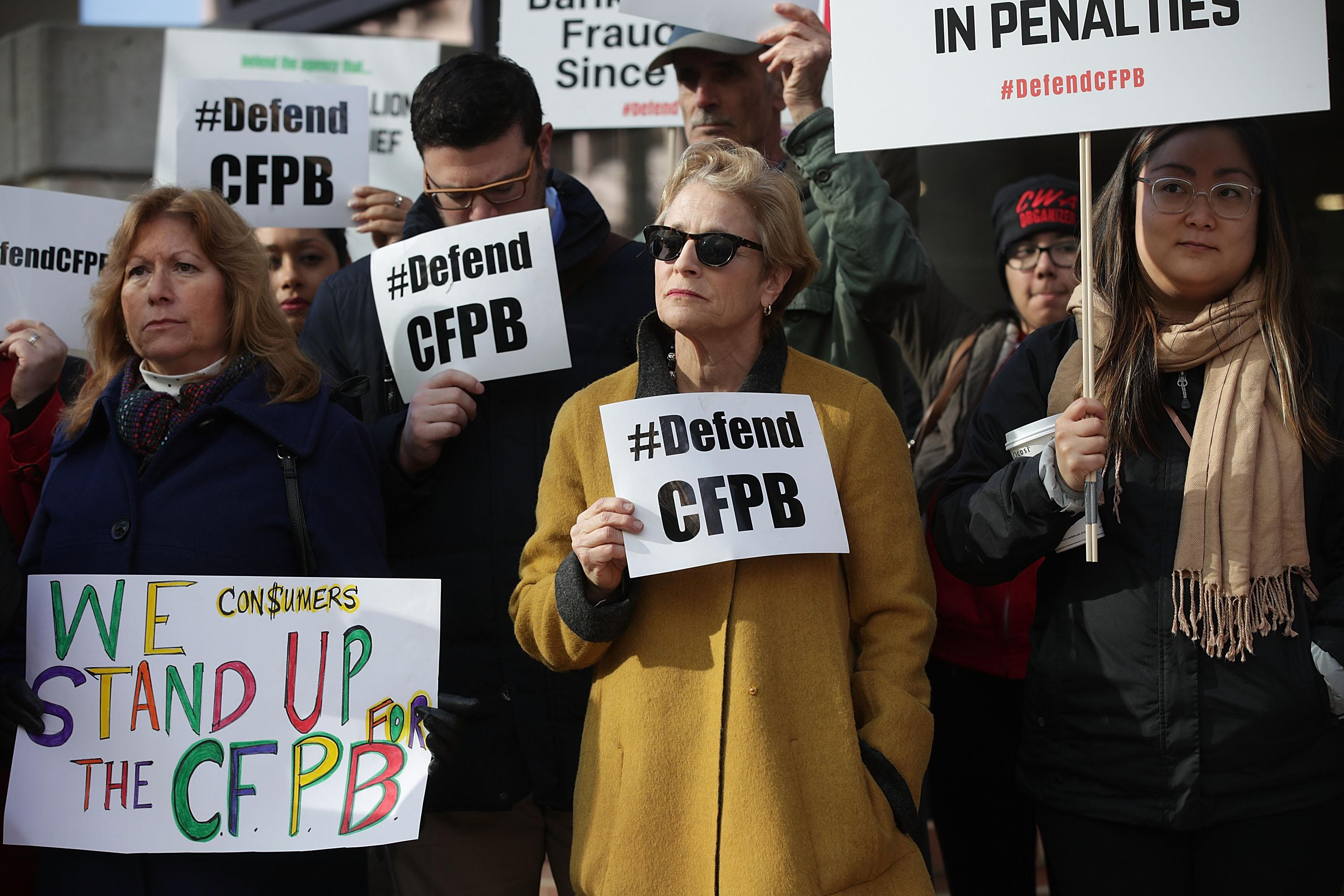 WASHINGTON, DC - NOVEMBER 27:   Supporters of the Consumer Financial Protection Bureau hold signs as they gather in front of the agency November 27, 2017 in Washington, DC. President Trump has picked White House Budget Director Mick Mulvaney as the acting director after former director Richard Cordray stepped down and named his chief of staff Leandra English as acting director, setting up a possible court battle over who will lead the agency.  (Photo by Alex Wong/Getty Images)