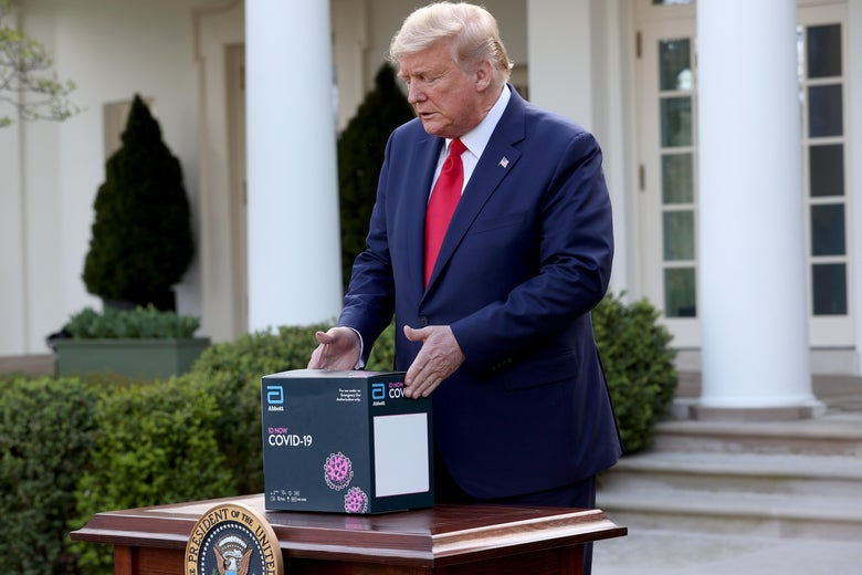 Donald Trump sets down a COVID-19 test kit on a table.