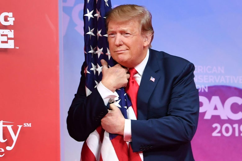 Trump hugs the U.S. flag as he arrives to speak onstage.