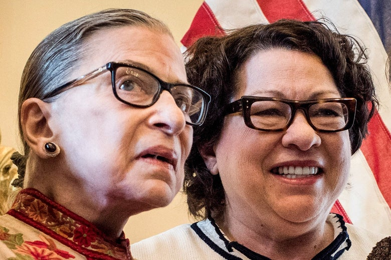 Sotomayor smiles next to Ginsburg, with an American flag in the background.