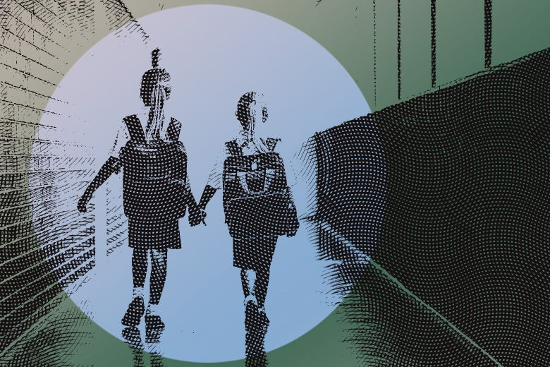 Two young girls wearing school uniforms and backpacks walk down a hallway holding hands