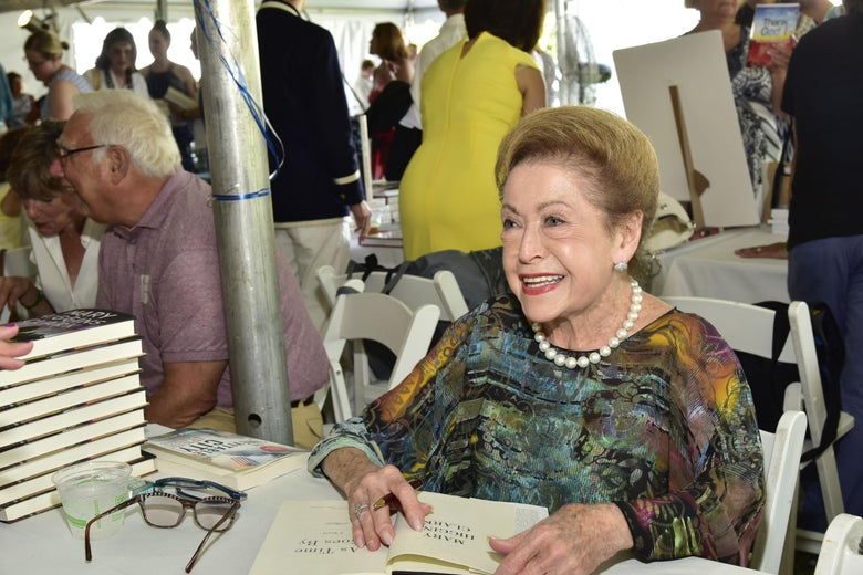 Mary Higgins Clark sits at a folding table with a stack of her books on it. She has one book open to sign, and is smiling.