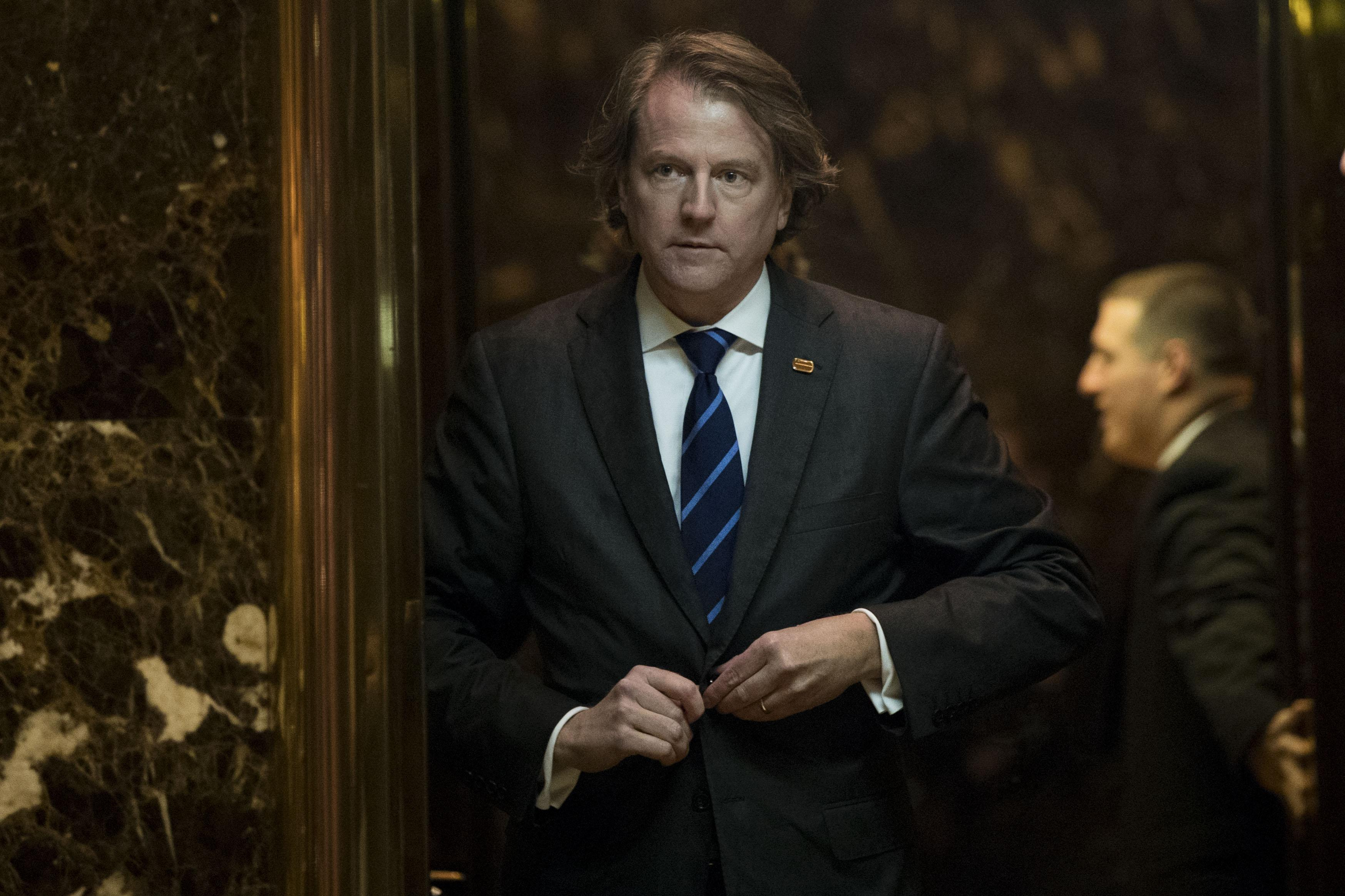 Don McGahn buttons his suit jacket as he gets into an elevator.