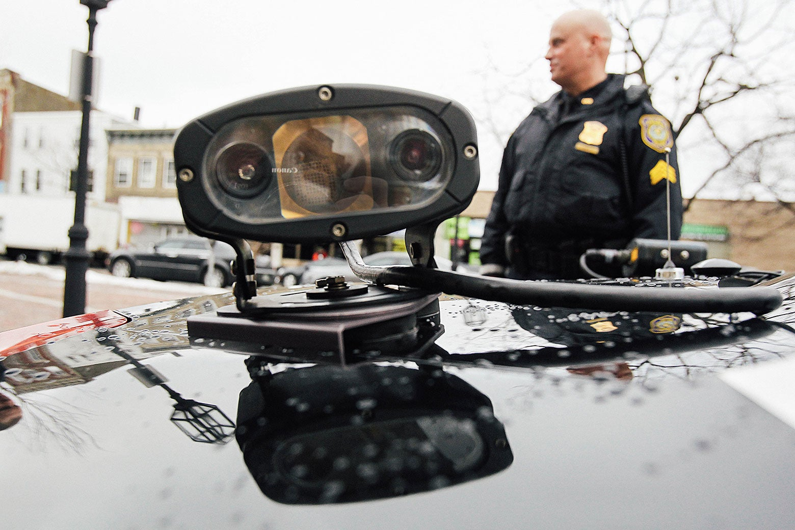 A police sergeant stands beside a cruiser equipped with an automatic license plate reader in Chelsea, Massachusetts.