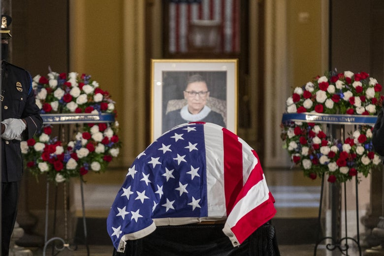 RBG's casket draped in an American flag in front of Ginsburg's portrait flanked by two wreaths.