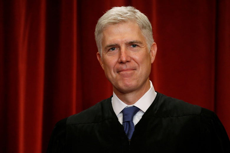 Justice Neil Gorsuch in robes against a red curtain.