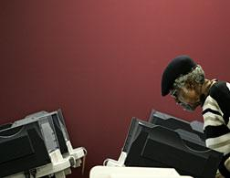 A woman votes using an electronic voting machine. Click image to expand.