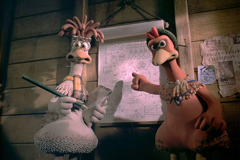 Two stop-motion animated chickens stand in front of a blueprint.