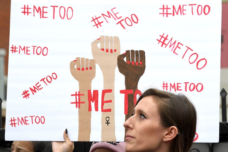 A woman holds a sign during #MeToo march.