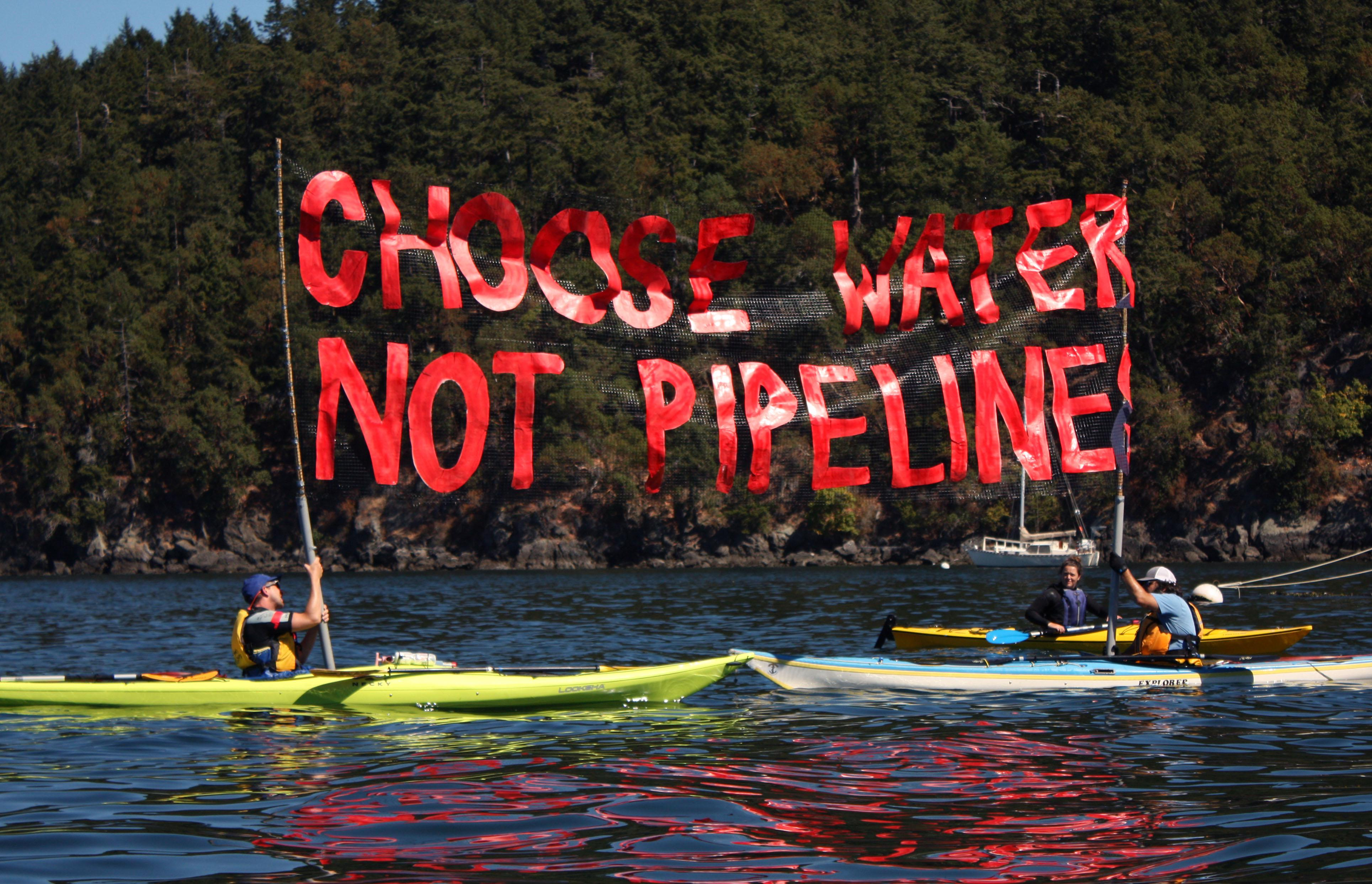 "Activists hold up a banner during a water-based ""pipeline resistance training camp."""