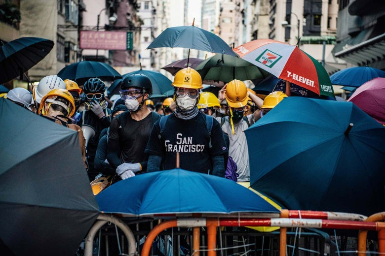 Masked protesters stand behind a makeshift barricade on July 28 in Hong Kong.