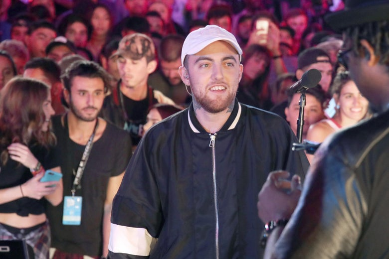 Mac Miller wears a white hat and stands in front of a crowd.