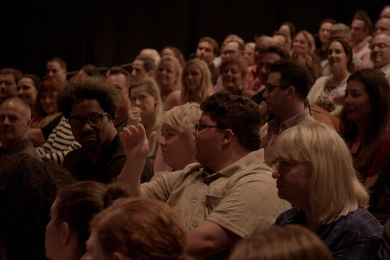 A theater audience. W. Kamau Bell and Gavin Grimm are seated towards the front; Susan Sarandon is visible in the back.