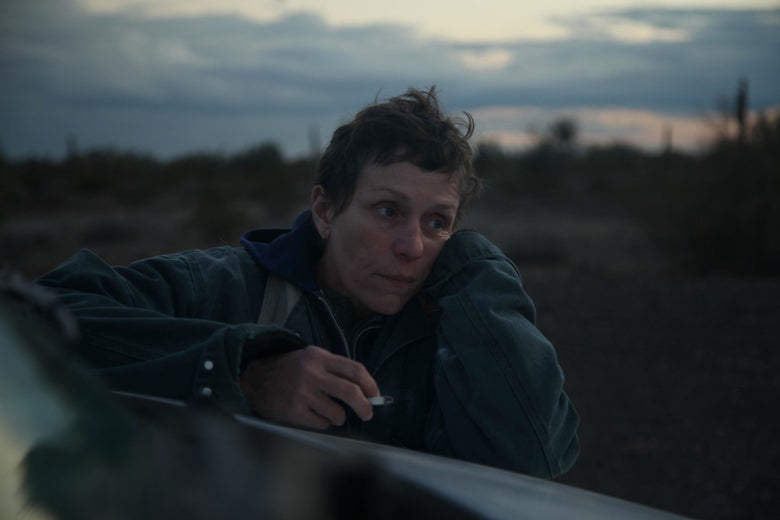 Frances McDormand in short hair, leaning on the hood of a van, a cigarette in one hand