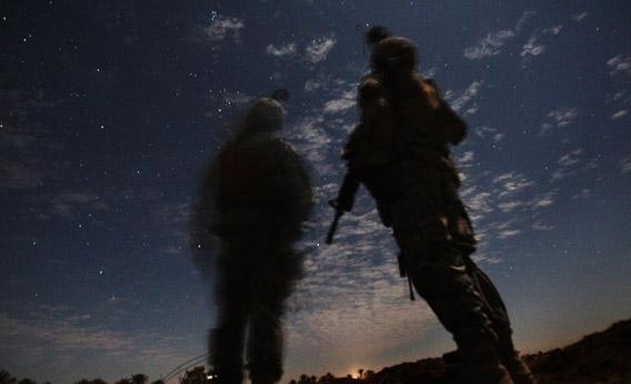 U.S. Army soldiers from Charlie Company 2-5 Cavalry Regiment watch for illumination rounds during a night patrol near Camp Kalsu in Tunis, Iraq, 20 miles south of Baghdad on December 5, 2011.