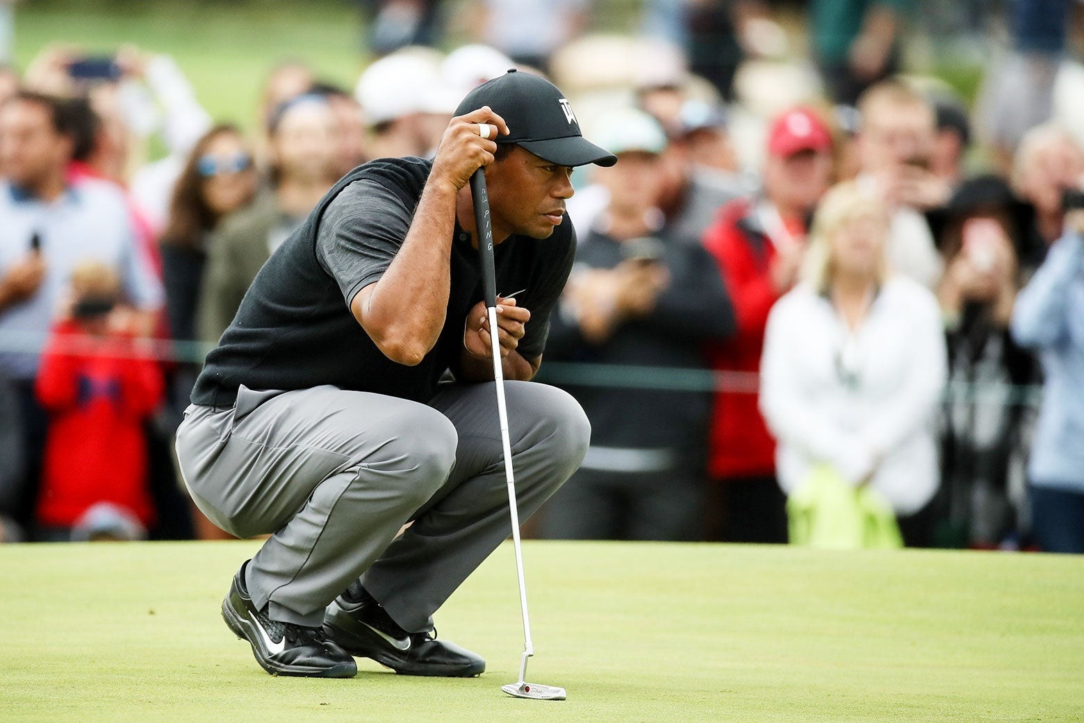 Tiger Woods lines up a putt on the 10th green during the third round of the BMW Championship.