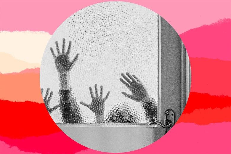 Children's hands grasping at the window in a door
