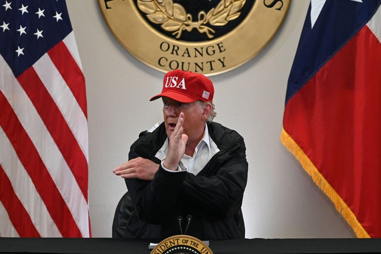 Trump makes an X with his arms as he speaks at a podium