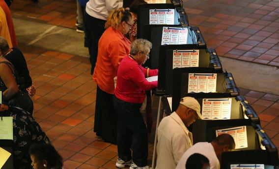 Early voters fill out their ballots in Miami, Florida as they cast their vote in the presidential election on the first day of early voting on Saturday.