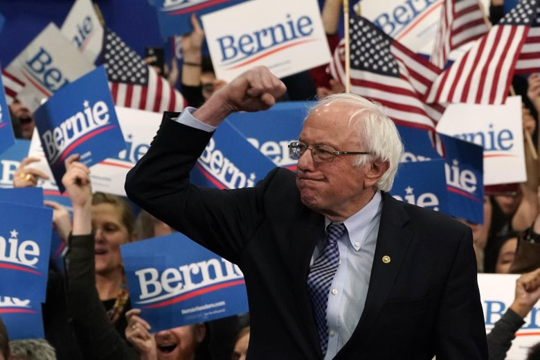 Bernie Sanders raises his fist, with a crowd of supporters behind him.