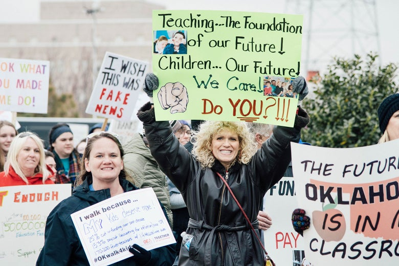 """Protesting teachers hold up signs saying things like, """"The future of Oklahoma is in the classroom."""""""