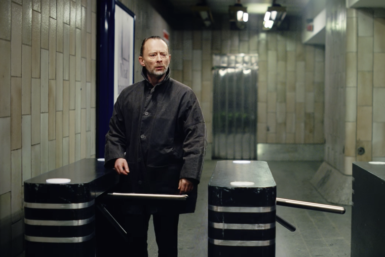 Thom Yorke at a subway turnstile, looking puzzled.
