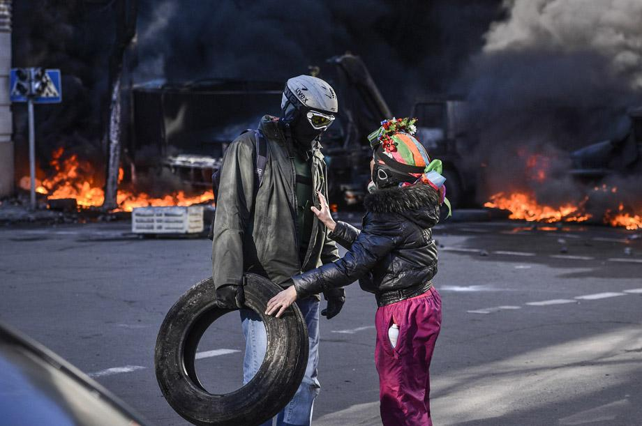 People speak near a barricade on fire during clashes between protesters and government police in Kiev on Feb. 18, 2014.