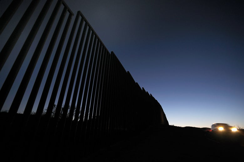 At twilight, a Border Patrol agent drives by a fence at the border.