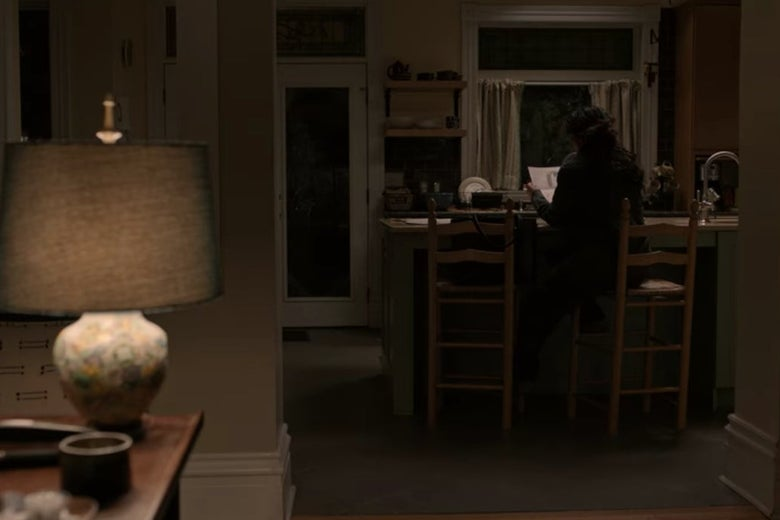 Dr. Kim sits on a tall chair in front of a kitchen counter in a dark house.