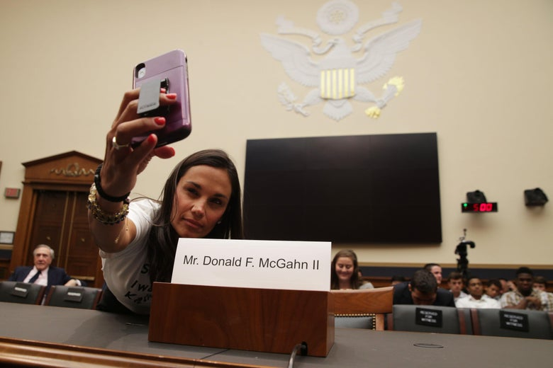 Shapiro leans over the witness table to take a selfie with the empty seat for McGahn. Behind her, a TV and timer on the wall and several people seated for the hearing.