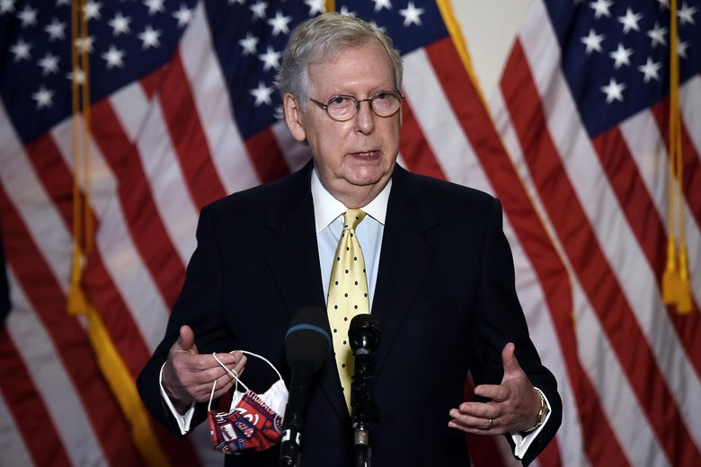 McConnell speaks at a mic, standing in front of American flags