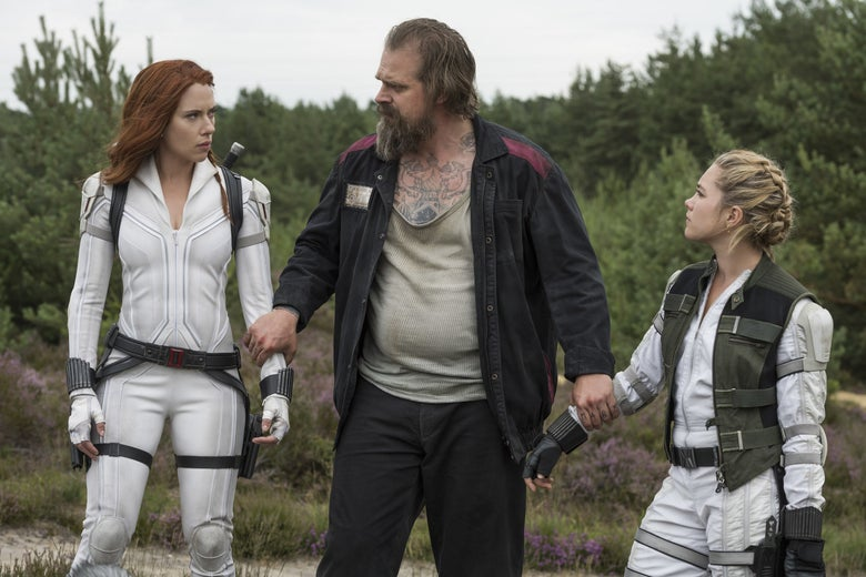 Black Widow and her sister, in white jumpsuits, on either side of their father, Alexei.