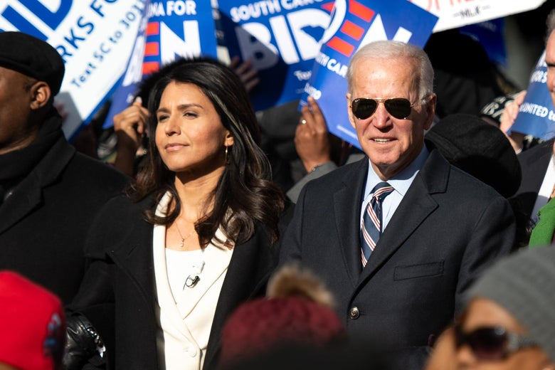 Tulsi Gabbard and Joe Biden march together in the sunshine surrounded by other marchers. Biden is wearing sunglasses.