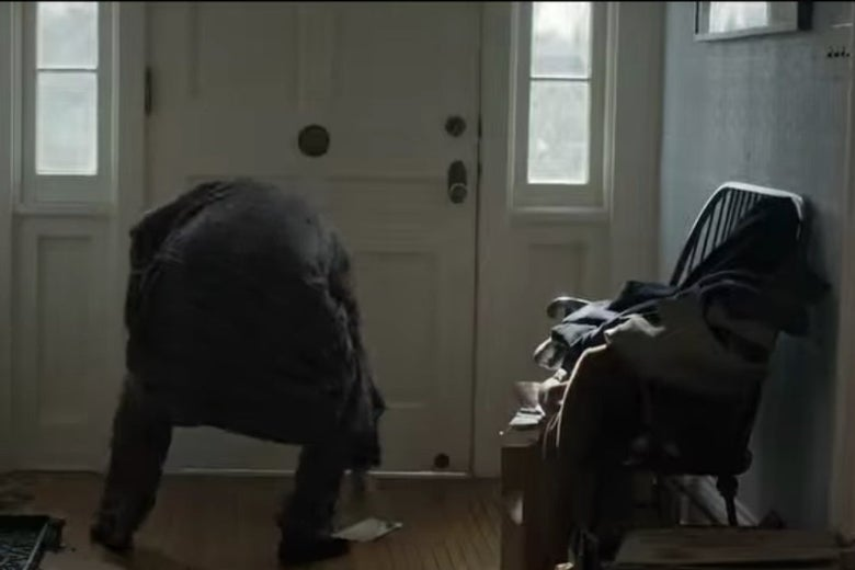 Bill bends down to pick something up in front of his front door, next to a chair piled with clothes and other stuff.