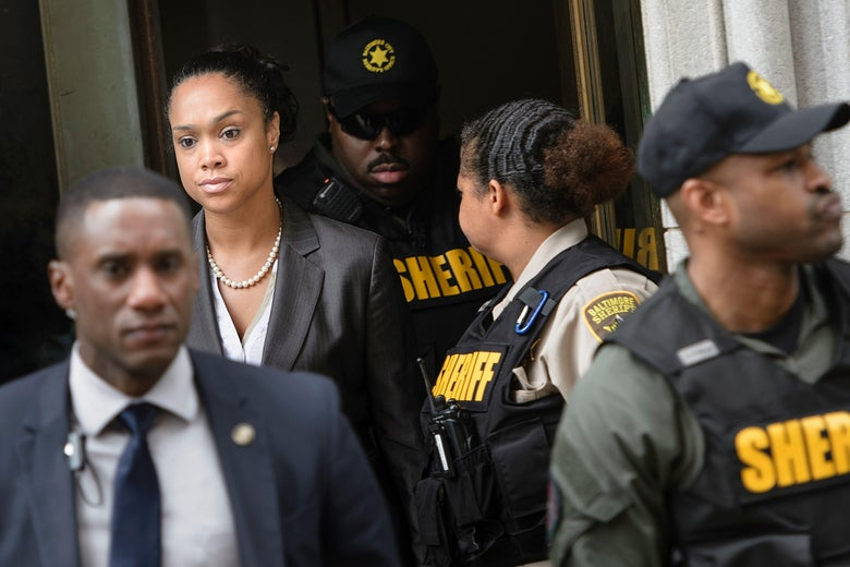 Marilyn Mosby leaves a courthouse surrounded by sheriff's deputies and police