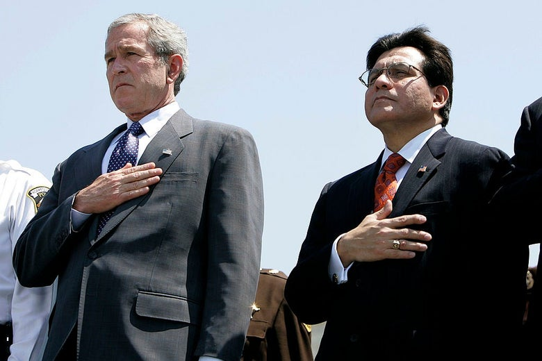 George W. Bush and Alberto Gonzales stand side by side against a blue sky with their hands over their hearts.