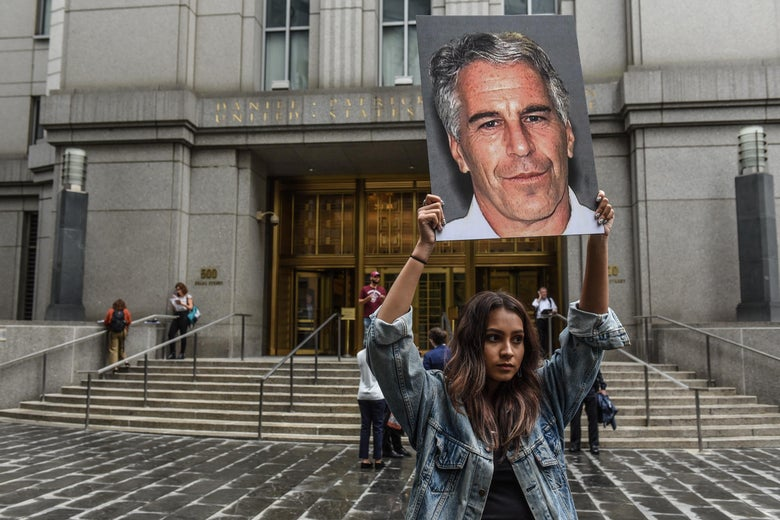 A protester holds signs of Jeffrey Epstein's face in front of the federal courthouse in New York.