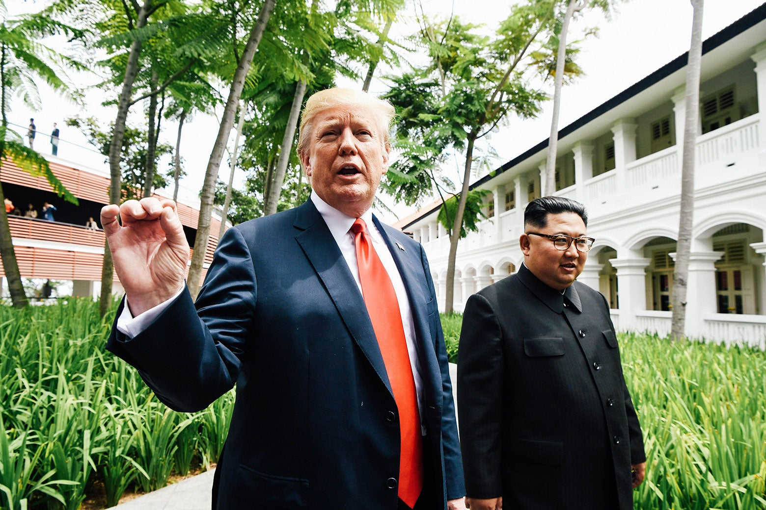 U.S. President Donald Trump speaks to the media as he walks with North Korean leader Kim Jong-un during a break in talks at their summit at the Capella Hotel on Sentosa island in Singapore on Tuesday.