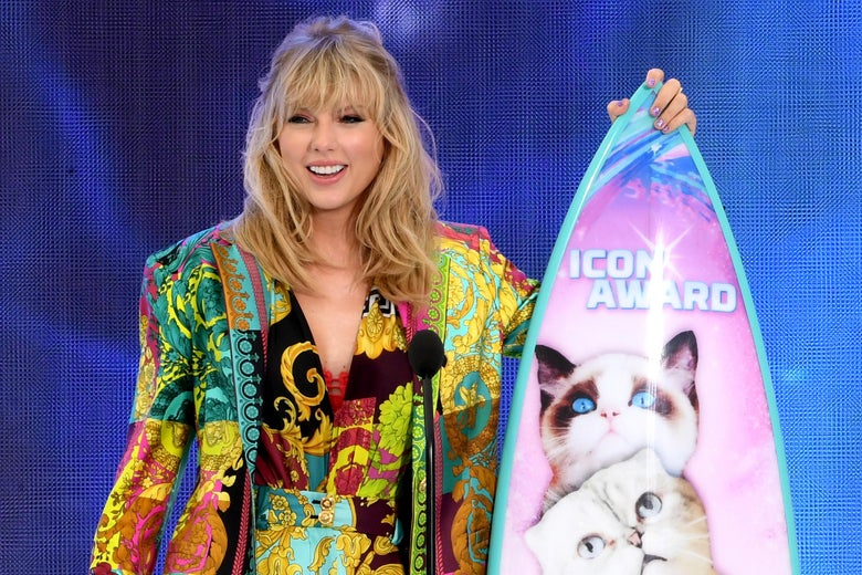 Taylor Swift holds a cat-covered surfboard.