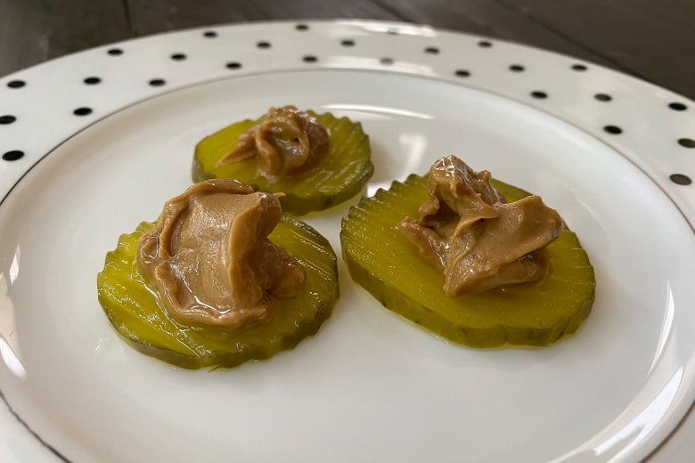 Pickles on a plate with peanut butter on top of them.