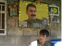 A PKK member under a photo of imprisoned PKK leader Abdullah Ocalan. Click image to expand.