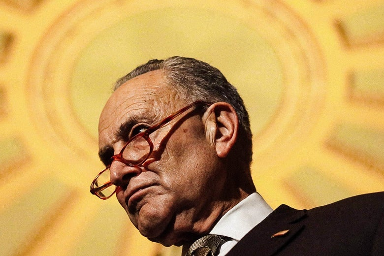 Schumer is seen frowning from below against the gold backdrop of the Capitol dome.