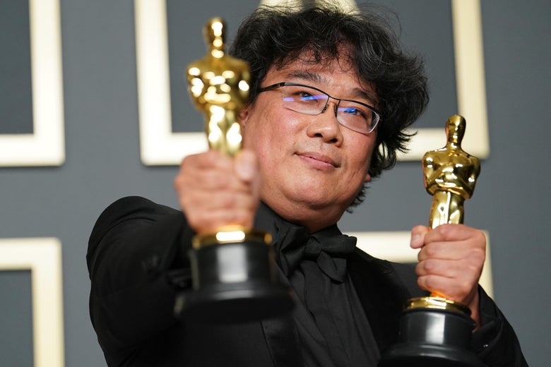 Bong Joon-ho poses in the press room, holding up two Oscar statuettes.